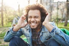 Close-up outdoor portrait of handsome african man with afro haircut holding hands on headphones while listening to music. And being excited, sitting in park royalty free stock photography