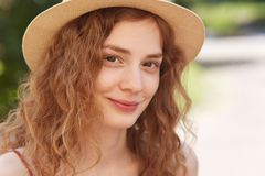 Close up outdoor portrait of young attractive girl wearing straw hat, has foxy wavy hair, looking directly at camera, has charming royalty free stock photography