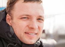 Close up outdoor portrait of young smiling man. In cold season Stock Images