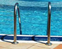 Outdoor swimming pool handrails in the sunshine. Close up of an outdoor swimming pool handlebars in the summer sun royalty free stock photos