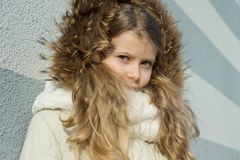 Close-up of an outdoor winter portrait of child, blonde girl with curly hair of 7,8 years in fur hood Royalty Free Stock Photos