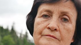 Close up outdoors portrait of sad senior woman with wrinkled face and short dark hair on mountain hill with green forest. And grey sky background, HD stock video