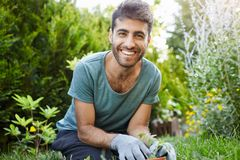 Close up outdoors portrait of young attractive bearded caucasian male gardener in blue t-shirt smiling in camera. Planting seeds in garden, watering plants Royalty Free Stock Photography