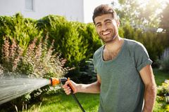 Close up outdoors portrait of young good-looking caucasian male gardener smiling in camera, watering plants, spending. Summer in countryside house Royalty Free Stock Image