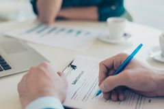 Close up overhead above top photo of man`s hands signing a contract contract business partnership real estate agent recruiter con. Cept stock photo