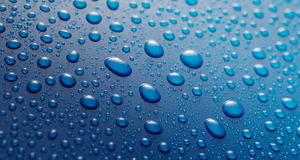 Close up overhead view of condensation. Spread across shiny blue surface Stock Photography