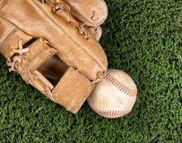 Close up overhead view of old leather baseball and mitt on grass Royalty Free Stock Photos
