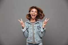 Close-up of overjoyed charming brunette woman showing peace gest Royalty Free Stock Photos