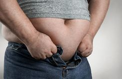 Close up of overweight man trying to wear small jeans royalty free stock photo
