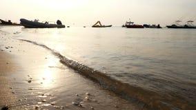Close-up, overzeese branding, getijde, overzeese golven op het zandstrand in de stralen van de zon, op de achtergrond van amid va stock videobeelden