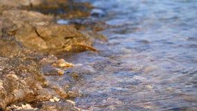 Close-up, overzeese branding, getijde, overzeese golven op het zandstrand in de stralen van de zon, warme de zomerzonsondergang, stock video