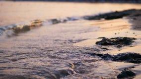Close-up, overzeese branding, getijde, overzeese golven op het zandstrand in de stralen van de zon, warme de zomerzonsondergang, stock footage