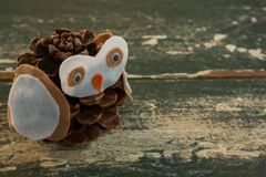 Close up of owl decoration made with pine cone. On wooden table stock image