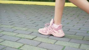 Close-up p?s f?meas nas sapatilhas cor-de-rosa ? moda menina que anda na rua com pavimento Luz do dia ensolarada natural filme