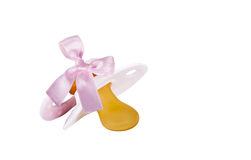 Close up of pacifier. With pink ribbon as parenthood concept Royalty Free Stock Photos