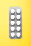 Close-up packaging for pills on a yellow background. Prescripted drugs, tablets, painkillers in a capsule. Medicinal supplement. Painkillers in a gray package Stock Images