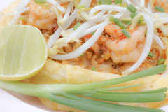 Close up of padthai covered by omelet. Colse up of padthai covered by omelet with shrimp, lemon, scallion, & bean sprouts stock image