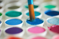 Close up paint brush and paints. Paint brush up close on watercolor paints Royalty Free Stock Images