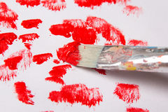 Close up of paint brush with red paint strokes over white Stock Image