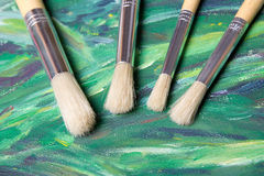 Close up of paint brushes on green canvas background Royalty Free Stock Photos