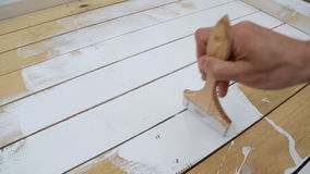 Close-up of a paintbrush painting in white wooden boards. stock video footage