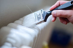 Close up of painter arm painting a heating radiator with paint roller. Professional Workman Hand holding Dirty Paintbrush. Royalty Free Stock Images