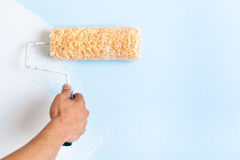 Close up of painter arm painting a wall Royalty Free Stock Photos