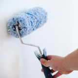 Close up of painter arm painting a wall with paint roller. Professional Workman Hand holding Dirty Paint roller. Stock Photo