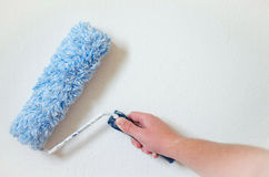 Close up of painter arm painting a wall with paint roller. Professional Workman Hand holding Dirty Paint roller. Royalty Free Stock Photography