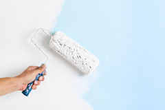 Close up of painter hand painting a wall Royalty Free Stock Photo