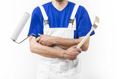 Close up of painter man with paint roller and brush Stock Photos