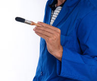 Close Up Painters Hand With Brush -Horizontal. A close up of a painter wearing a blue jumpsuit with a black bristled brush in his right hand Stock Image