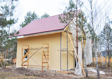 Close up on Painting and Plastering Exterior House Wall. Building House Construction with Metal Roof in the Forest. Royalty Free Stock Image