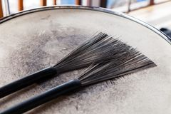 Close-up of a pair of black drum brushes on a white shabby drum. Concept concert, live music, performance, musical evening in a royalty free stock photos