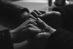 Close-up pair of holding hands lovers. In monochrome Stock Photos