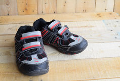 Close up of a pair of kids sport shoes on wood panels.  stock images