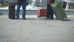 Close-up of a pair of legs, couple with luggage meets a water taxi on the canal in Venice