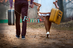 Close-up of a pair of newlyweds walking with suitcases Stock Photo