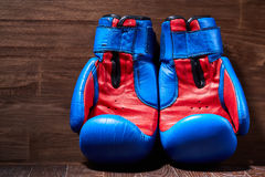 Close-up of the pair of red and blue boxing gloves on the wooden plank. Horizontal photo of colorful sportwear against brown background. Boxing backgrounds and Royalty Free Stock Images