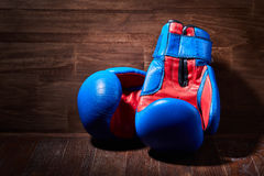 Close-up of the pair of red and blue boxing gloves on the wooden plank. Horizontal photo of colorful sportwear against brown background. Boxing backgrounds and Stock Photos