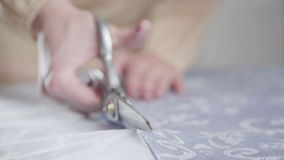 Close-up of a pair of scissors in female hands. Scissors cut cloth. stock video footage