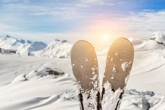 Close-up pair of skis on mountain winter resort with ski-lift and beautiful winter mountain panoramic scenic view.  royalty free stock image