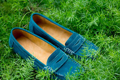 Close up of a pair of turquoise women`s shoes in grass.  Royalty Free Stock Images