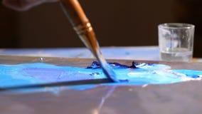Close-up Palet met blauwe verf Een borstel verschijnt, neemt blauwe verf op en mengt kleur 4K langzame mo stock video