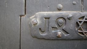 Close-up pan over door Star Magen or Shield of David. Close-up pan over door with Star Magen or Shield of David into a steel frame placed on textured colorful stock video
