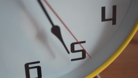 Close up pan shot of clock face with ticking second hand. Big yellow home clock on table stock video footage