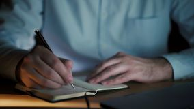 Close up pan shot of male hands writing in small notebook stock footage