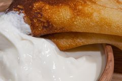 Pancake on a plate with sour cream closeup. Close-up of a pancake with sour cream in and a clay dish on an oak table Stock Images