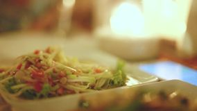 Close up of papaya salad and fried rice with vegetebles in the outdoor cafe on blurred bokeh background, Thailand stock video footage
