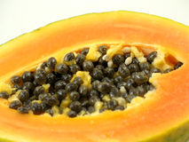 Close-up of papaya seeds on white. Close-up of black papaya seeds in fleshy yellow and orange fruit, on white Royalty Free Stock Image
